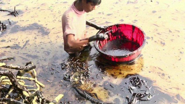 A man tries to collect oil from the water