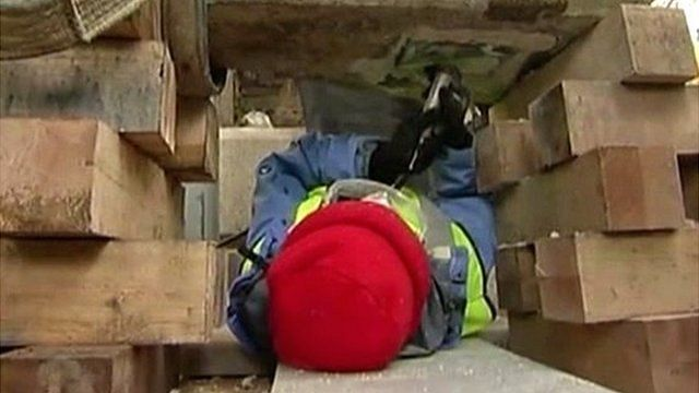 A construction worker removing a time capsule from granite