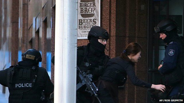 Woman fleeing Sydney cafe siege with three armed Australian police officers