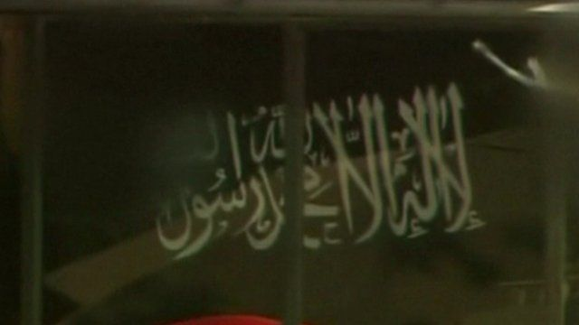 "A black flag bearing the white Arabic text of the ""shahada"", the basic statement of the Islamic faith, being held in the Lindt Chocolat Cafe, Sydney, 15 December 2012"