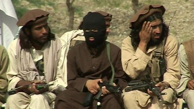 Taliban members sitting with guns