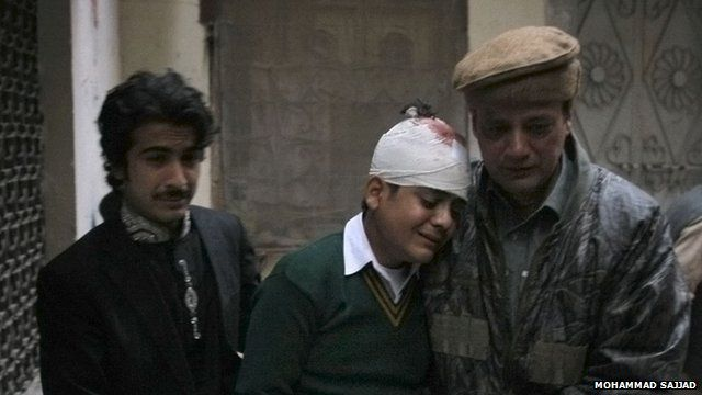 The uncle and cousin of injured student Mohammad Baqair, center, comfort him as he mourns the death of his mother who was a teacher at the school