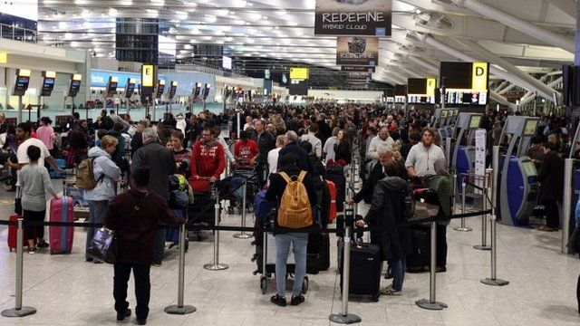 People wait at Terminal 5 of Heathrow Airport as dozens of flights have been cancelled nationwide and many others delayed after a computer failure at the headquarters of air traffic control company Nats
