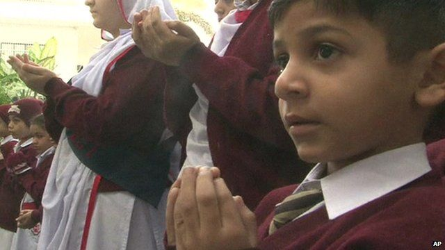 Close up of schoolboy in Pakistani city of Karachi saying prayers for victims of Peshawar school attack