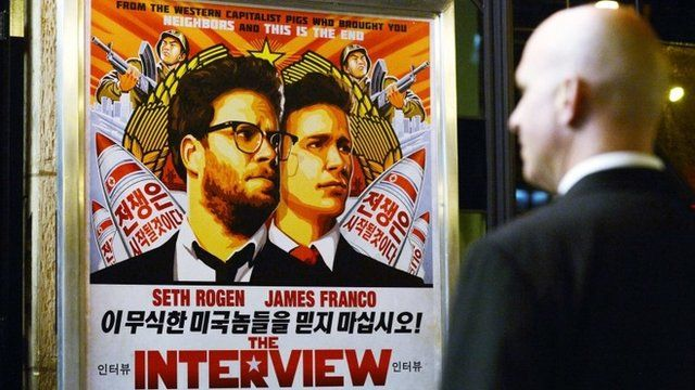 A security guard stands near a poster for The Interview