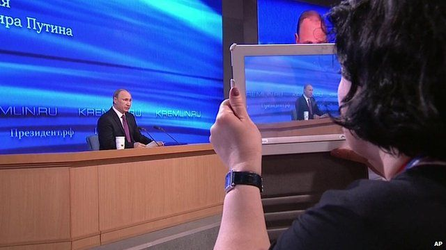 Woman using tablet to photograph Russian president Vladimir Putin during his end-of-year news conference