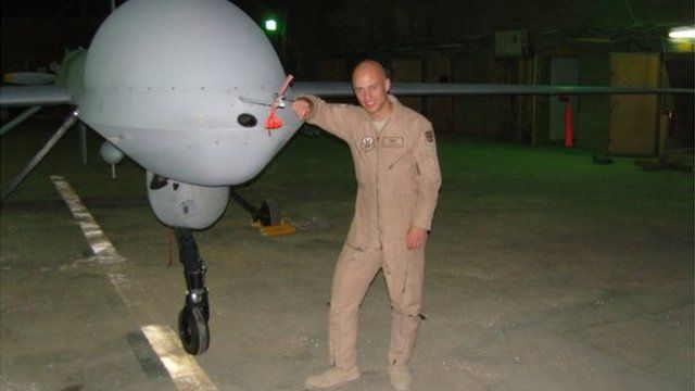 Brandon Bryant standing next to the drone he operated