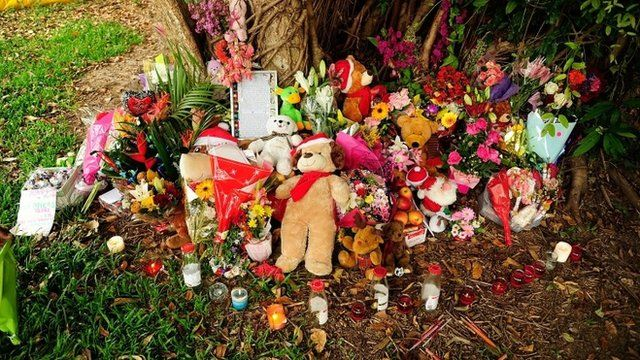 A memorial of flowers, toys and candles is seen in a park next to the home