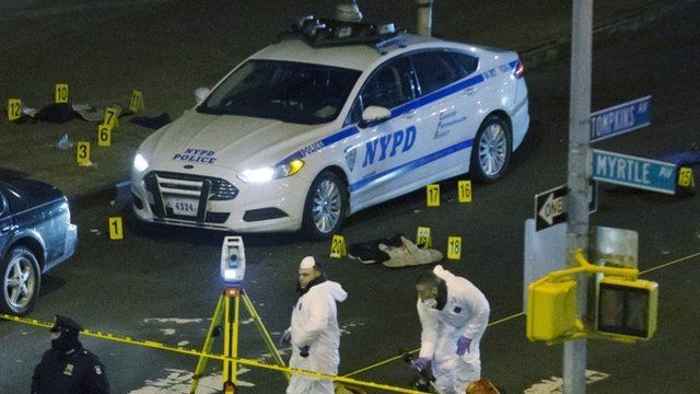 Investigators work at the scene where two NYPD officers were shot