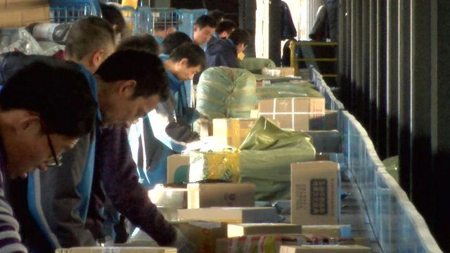 Workers with parcels on a conveyer belt