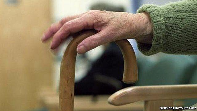 Elderly patient's hand on walking stick