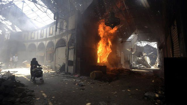 A woman walks past a burning shop in a market in the Old City of Homs, May 2014