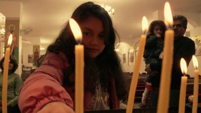 Iraqi Christian child refugee lights a candle in Church