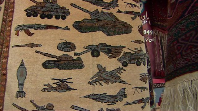 Afghan rug covered in military vehicles
