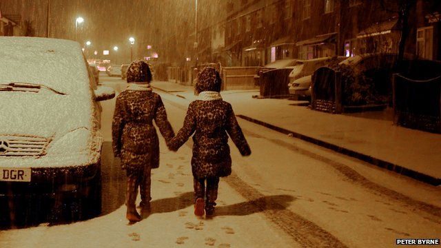 Maisy Byrne, aged nine, (left) and sister Lulu Byrne, aged seven, have fun as snow falls on Boxing Day in Gateacre, Liverpool. Picture date: Friday December 26, 2014.