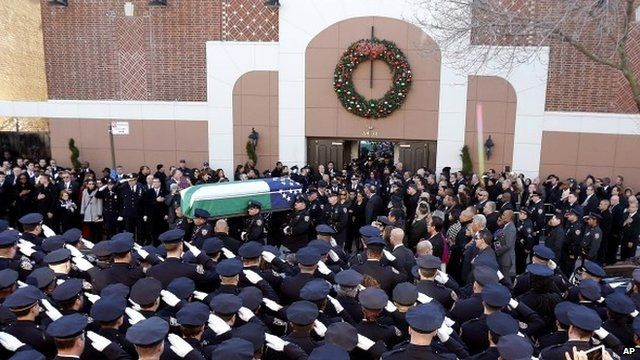 Police officers saluting coffin outside church