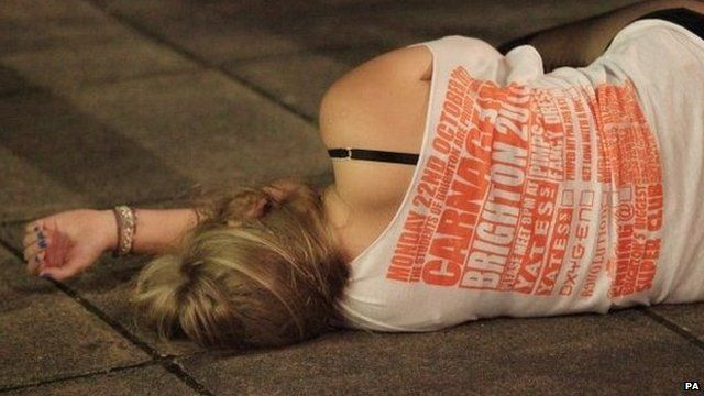 Young woman lies on the pavement in Brighton, having drunk too much