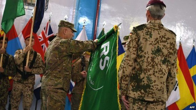 Gen John Campbell opens the flag of Resolute Support during a ceremony at Isaf headquarters in Kabul on 28 December.