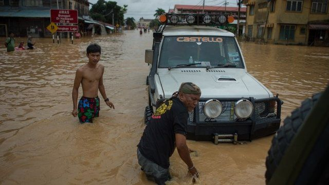 A local resident (C) measures the depth of floodwaters in Kota Bahru