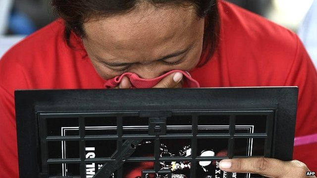 An Indonesian woman breaks down while holding a family picture of passengers onboard the missing plane