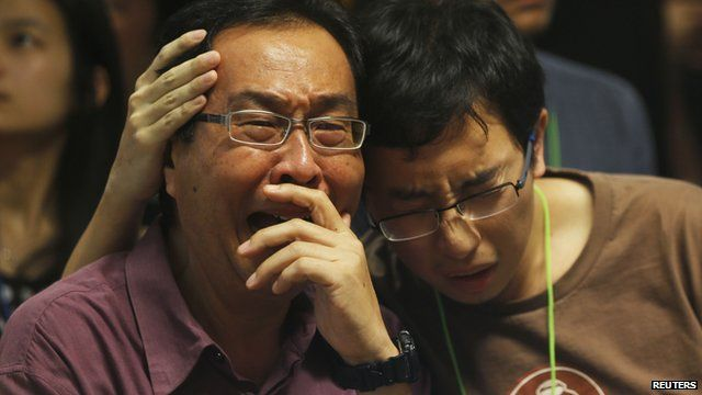 Relatives in Surabya crying as they watch news conference on missing flight QZ8501