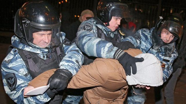 Police officers detain a supporter of opposition leader and anti-corruption blogger Alexei Navalny during a rally in central Moscow, Russia, 30 December 2014