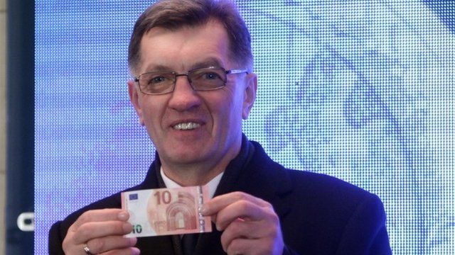 Lithuanian Prime Minister Algirdas Butkevicius withdraws euros from a bank machine during a ceremony in Vilnius, on January 1, 2015