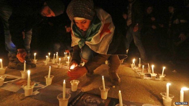 Activists light candles over pictures of war victims at a new year event in Salah al-Din, central Aleppo December 31 2014