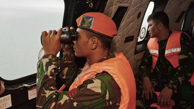 A crewmember of an Indonesian Air Force Super Puma helicopter of the 6th Air Squadron uses binoculars to scan the horizon during search operations for victims of AirAsia Flight QZ8501 over the Java Sea on January 1, 2015