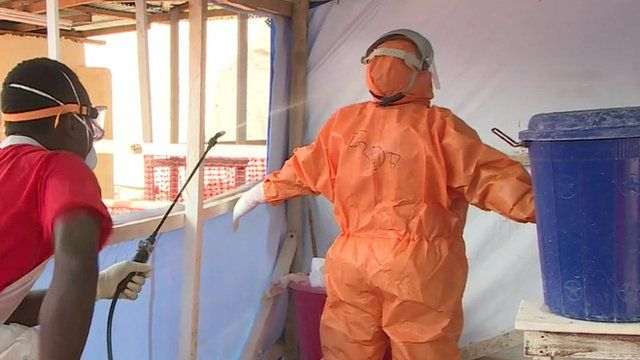 A worker is cleaned after treating Ebola patients