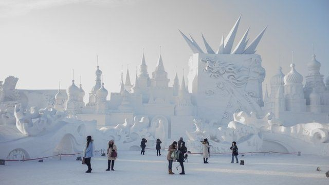 """Visitors look at snow sculptures during the 16th Harbin International Ice and Snow Festival in Harbin, northeast China""""s Heilongjiang province on January 5, 2015"""