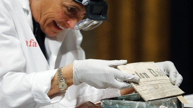 Conservator Pam Hatchfield removes a newspaper from a time capsule