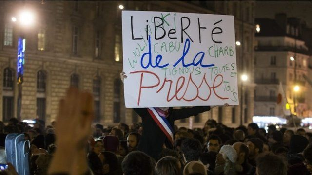 """A participant holds a placard with the words; """"Freedom of the Press"""", as thousands gather for a candle light vigil on Place de la Republique in central Paris hours after the attack by two gunmen on the """"Charlie Hebdo"""" headquarters in Paris, France, 07 January 2015"""