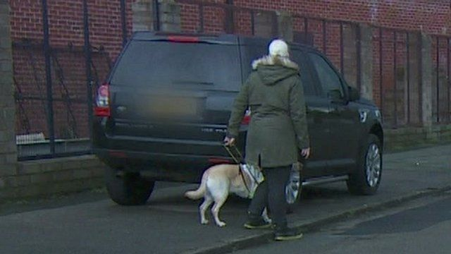 Blind person with guide dog blocked by car on pavement