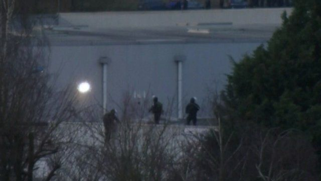 Figures on the warehouse roof