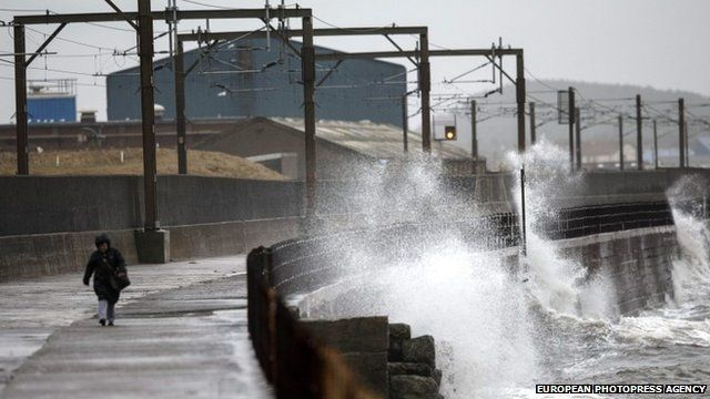 Wave crashes against the sea wall on the Ayrshire coast in Scotland