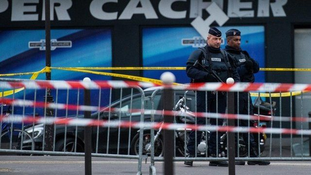 Police officers stand guard at the site of the attack on a kosher market on January 10, 2015 in Paris, France