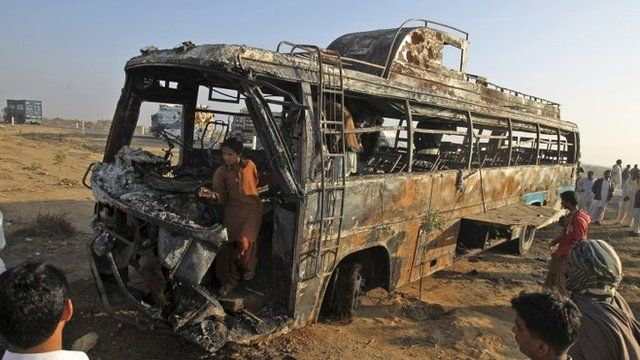 Pakistani gather around and inside the wreckage of a passenger bus