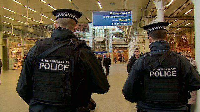 Backs of two British Transport Police on patrol at St Pancras station London