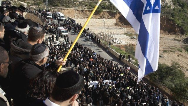 Mourners hold an Israeli flag while standing on a wall during the Jerusalem funeral of four men killed in an attack on a kosher supermarket in Paris