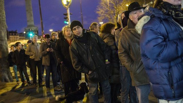 Members of the public queue at a newspaper kiosk in Paris