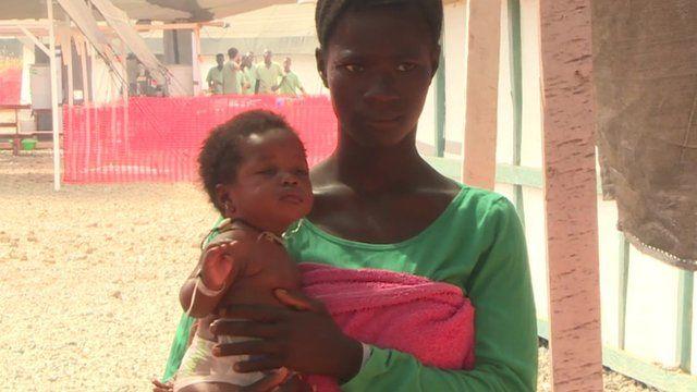 An Ebola survivor looks after a baby