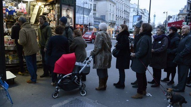 People wait outside a newsagents kiosk in Paris