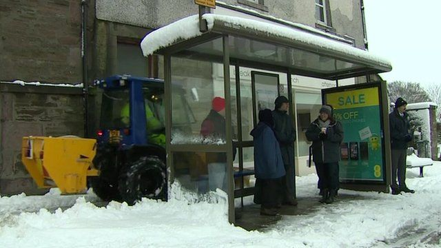 Gritter moving behind bus stop on a snowy street in Scotland
