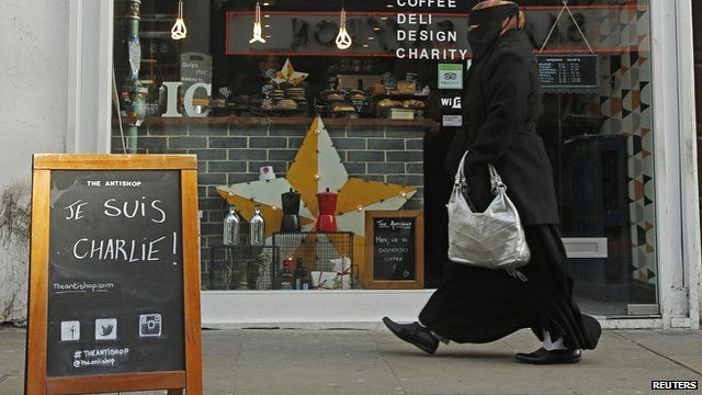 "A woman walks past an advertising board on which ""Je Suis Charlie!"" is written outside a cafe in Brick Lane"