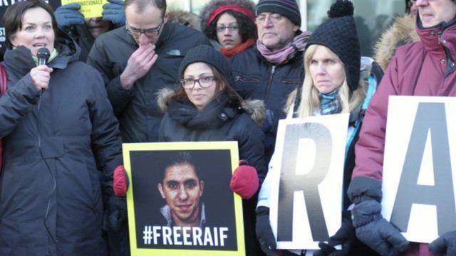 Ensaf Haidar holding a picture saying #freeraif