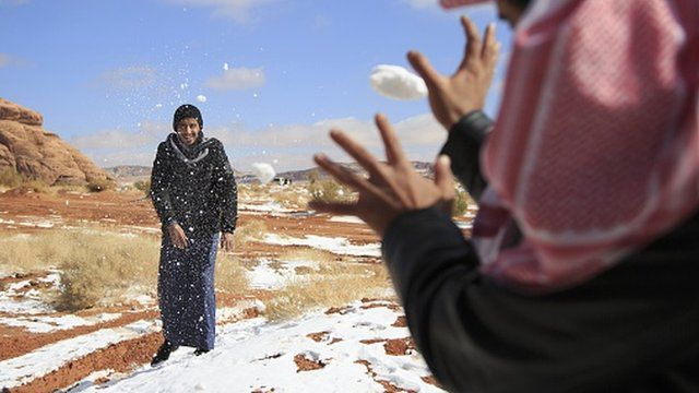 Men play with snow in Saudi Arabia