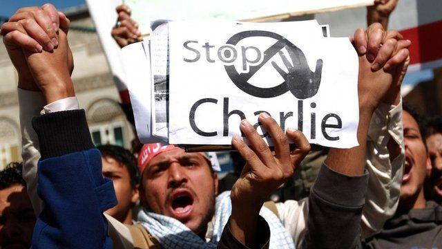 Yemeni protester holding up sign saying 'Stop Charlie'