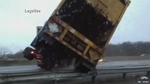 Close-up of tractor-trailer tipping over as it jack-knifes across New Jersey Interstate