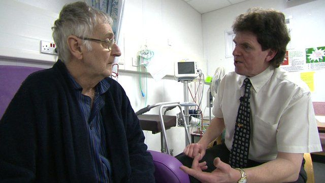 Richard Clarke of the Royal Voluntary Service speaking to a hospital patient